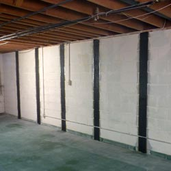 Carbon fiber straps adding strength to a foundation wall