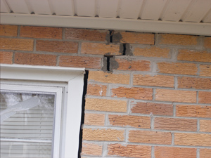 a foundation wall crack along the corner of a window.
